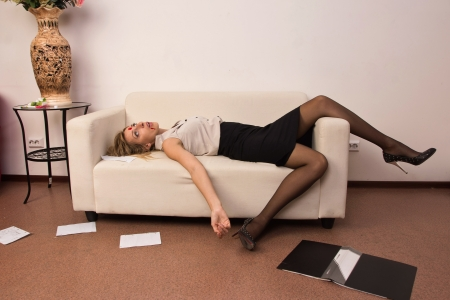 Crime scene imitation. Killed business woman lying on sofa photo