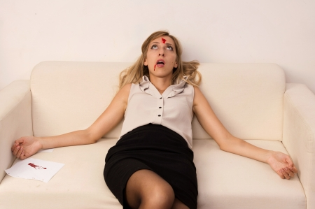 Crime scene imitation. Lifeless business woman lying on sofa photo