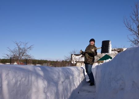 Man met een sneeuwschop in de winter tuin Stockfoto