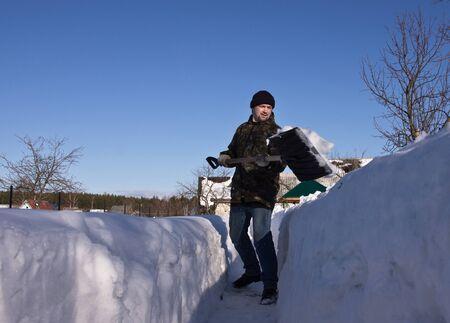 winter garden: Man with a snow shovel in winter garden   Stock Photo