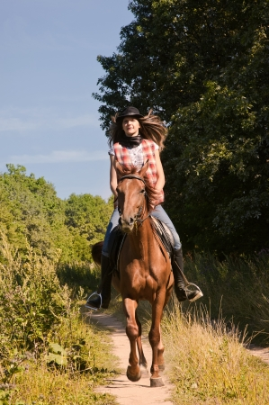 Young cowgirl riding a bay horse photo