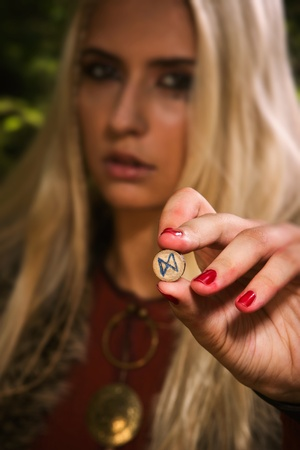 saga: Scandinavian witch pythoness with runes on a forest background