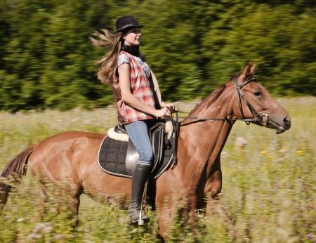 Jonge cowgirl berijden van een bruin paard