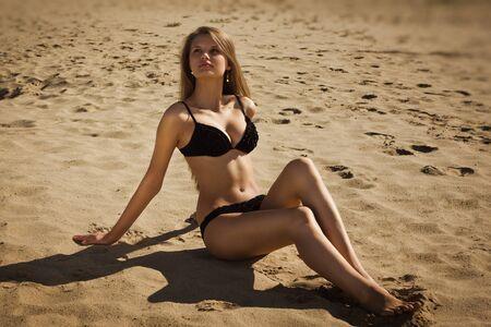 waterside: Attractive girl in a bikini on a sandy beach