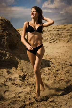 Attractive girl in a bikini on a sandy beach photo