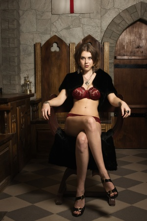 Sexy woman in a medieval castle interior photo