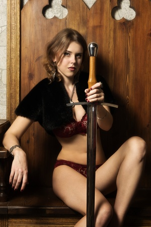 Sexy woman with a sword in a medieval castle interior photo