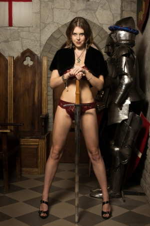 Portrait of the sexy woman with a sword in a medieval castle interior photo