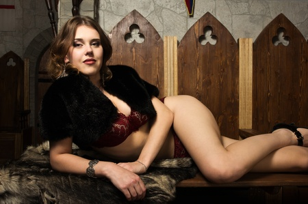 Portrait of the sexy woman in a medieval castle interior photo