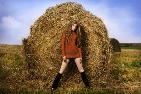 Pretty girl resting on straw bale on the autumn landscape background photo