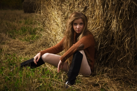cute young farm girl: Pretty girl resting on straw bale on the autumn landscape background Stock Photo