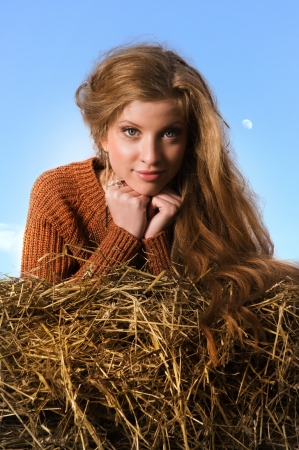 cute young farm girl: Pretty girl resting on straw bale on the blue sky background