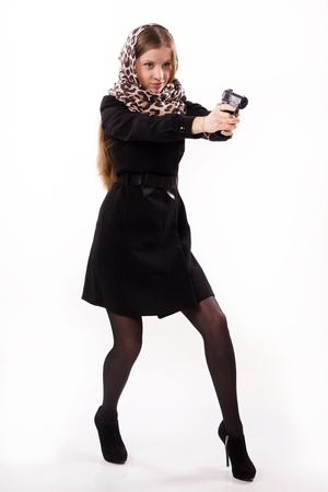 Spy girl in a black coat shoots a gun