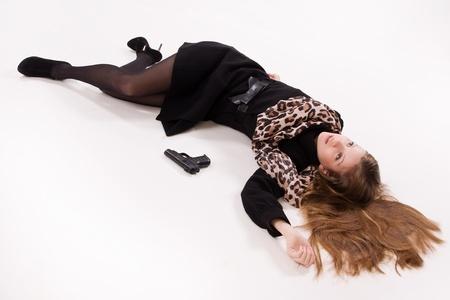 spy girl: Crime scene imitation. Spy girl with gun lying on the floor