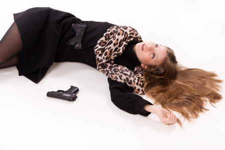 murdering: Crime scene imitation. Spy girl with gun lying on the floor