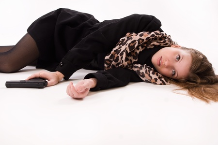 spies: Crime scene imitation. Spy girl with gun lying on the floor