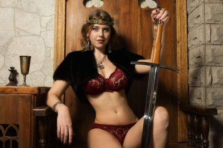 Sexy woman with a sword in a medieval castle interior Stock Photo - 16383093