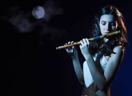 Sensuality beauty brunette plays a wooden flute Stock Photo - 16383145