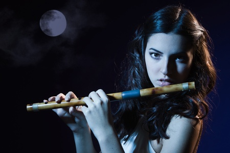 Sensuality beauty brunette plays a wooden flute Stock Photo - 16383112