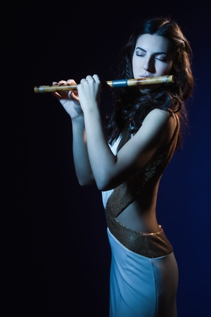 Sensuality beauty brunette plays a wooden flute Stock Photo - 16383140