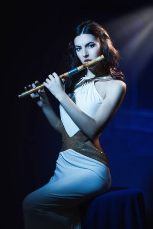 Sensuality beauty brunette plays a wooden flute Stock Photo - 16383099