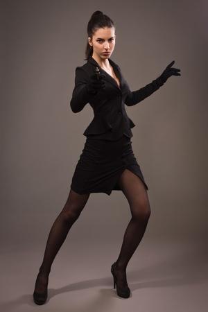 Spy girl in a black suit shoots a gun photo