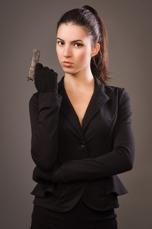 Spy girl in a black suit with gun photo