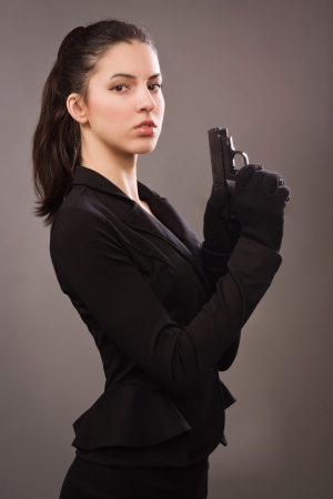 Spy girl in a black coat with gun   photo