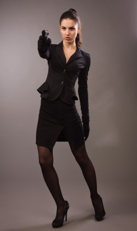 spy girl: Spy girl in a black suit shoots a gun Stock Photo
