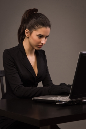 Spy girl in a black suit with laptop