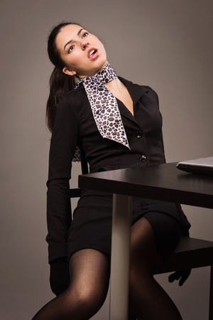 csi: Detective scene imitation. Lifeless woman in a black suit sitting on a office table Stock Photo