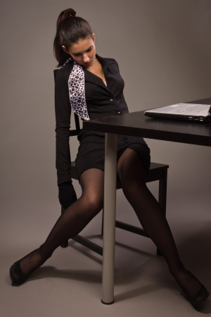 senseless: Detective scene imitation. Lifeless woman in a black suit sitting on a office table Stock Photo