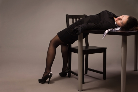 Detective scene imitation. Woman in a black suit lying on a table photo