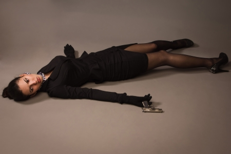 actress girl: Detective scene imitation. Woman in a black suit with gun lying on the floor Stock Photo