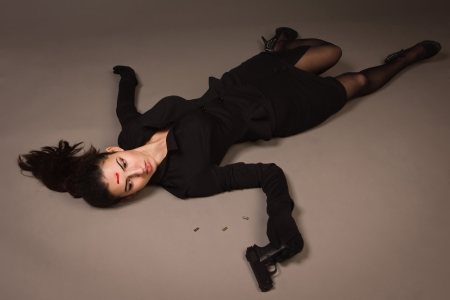 csi: Detective scene imitation. Woman in a black suit with gun lying on the floor Stock Photo