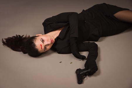 spy girl: Detective scene imitation. Woman in a black suit with gun lying on the floor Stock Photo