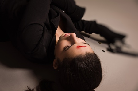 Detective scene imitation. Woman in a black suit with gun lying on the floor photo