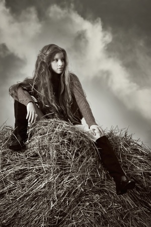 Pretty girl resting on straw bale on the dark sky background photo