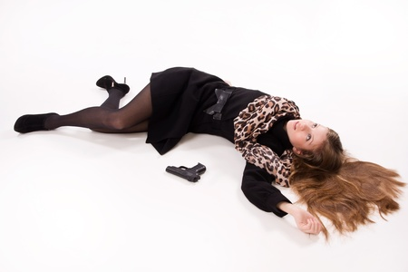 senseless: Crime scene imitation. Spy girl with gun lying on the floor