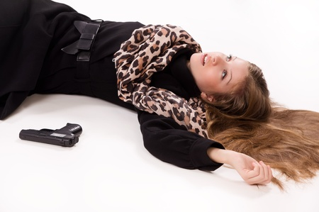 Crime scene imitation. Spy girl with gun lying on the floor photo