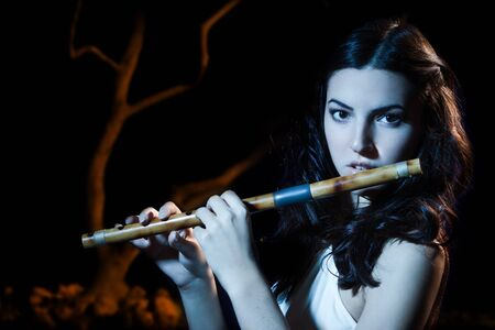 Sensuality beauty brunette plays a wooden flute Stock Photo - 16382913