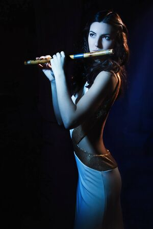 Sensuality beauty brunette plays a wooden flute Stock Photo - 16382938