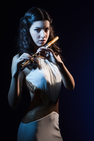 Sensuality beauty brunette plays a wooden flute Stock Photo - 16382899