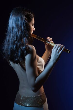 Sensuality beauty brunette plays a wooden flute Stock Photo - 16382872