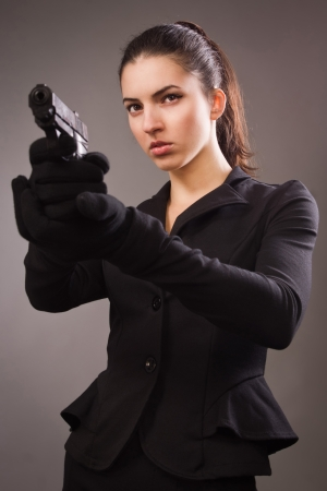 spies: Spy girl in a black suit shoots a gun Stock Photo
