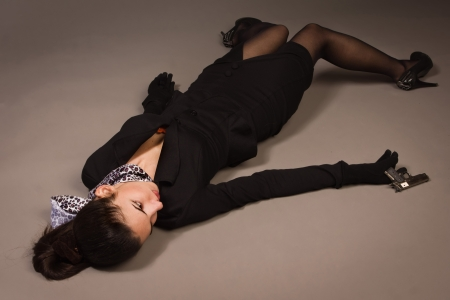 actress: Detective scene imitation. Woman in a black suit with gun lying on the floor Stock Photo