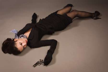 Detective scene imitation. Woman in a black suit with gun lying on the floor Stock Photo - 16382917