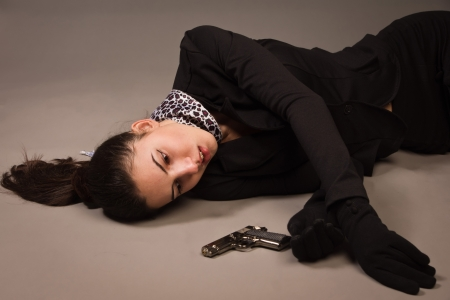 assassination: Detective scene imitation. Woman in a black suit with gun lying on the floor Stock Photo