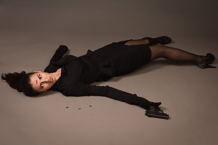 homicide: Detective scene imitation. Woman in a black suit with gun lying on the floor Stock Photo