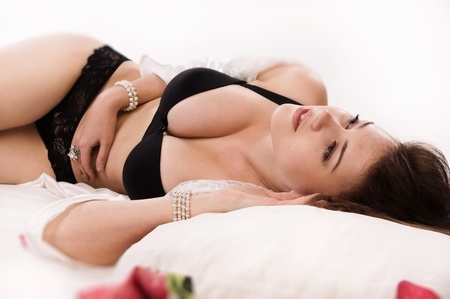 Attractive sexual brunette lying on the bed photo